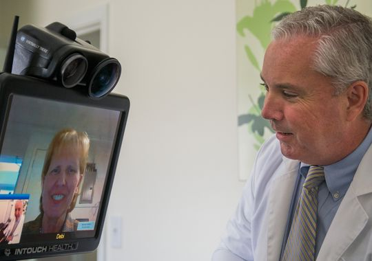 male physician using telehealth on patient